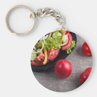 Fresh tomatoes and a part of a plate with salad basic round button keychain