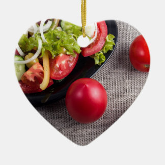 Fresh tomatoes and a part of a plate with salad ceramic heart ornament