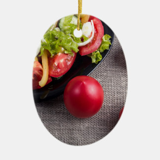 Fresh tomatoes and a part of a plate with salad ceramic oval ornament