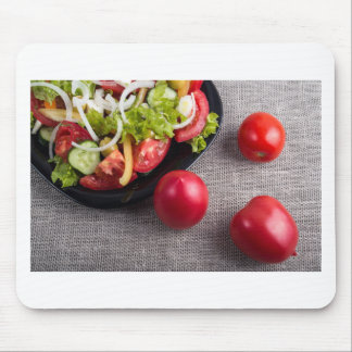 Fresh tomatoes and a part of a plate with salad mouse pad
