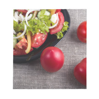 Fresh tomatoes and a part of a plate with salad notepad