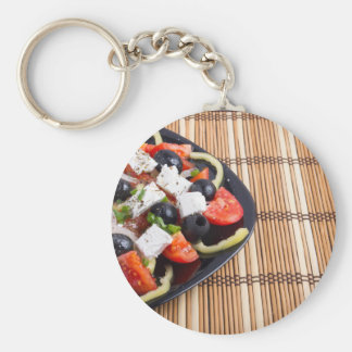 Fresh vegetarian salad in a black plate on a mat basic round button keychain