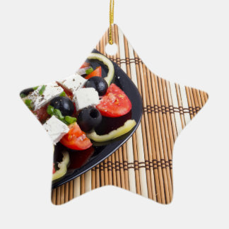 Fresh vegetarian salad in a black plate on a mat ceramic star ornament