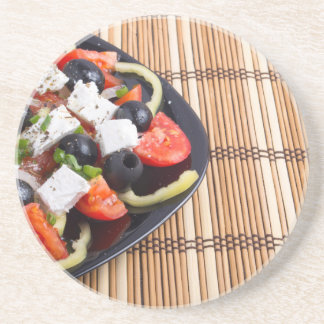 Fresh vegetarian salad in a black plate on a mat drink coasters