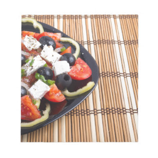 Fresh vegetarian salad in a black plate on a mat notepads