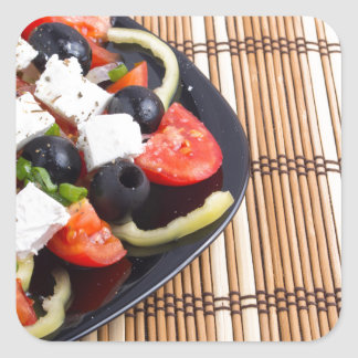 Fresh vegetarian salad in a black plate on a mat square sticker