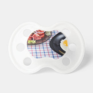 Fried egg with the yolk and tomato salad on fabric baby pacifiers