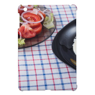 Fried egg with the yolk and tomato salad on fabric case for the iPad mini