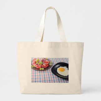 Fried egg with the yolk and tomato salad on fabric large tote bag