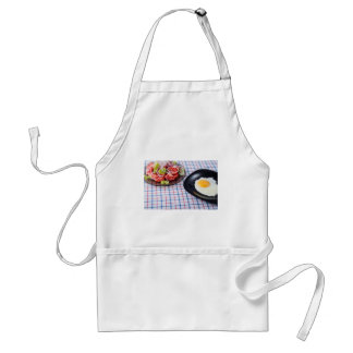 Fried egg with the yolk and tomato salad on fabric standard apron