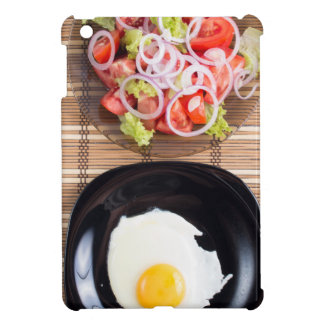 Fried egg with yolk on a black plate and a salad cover for the iPad mini