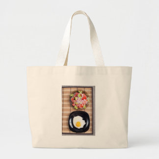 Fried egg with yolk on a black plate and a salad large tote bag