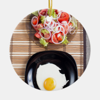 Fried egg with yolk on a black plate and a salad round ceramic ornament