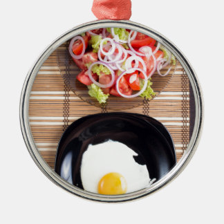 Fried egg with yolk on a black plate and a salad Silver-Colored round ornament