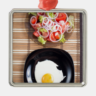 Fried egg with yolk on a black plate and a salad Silver-Colored square ornament