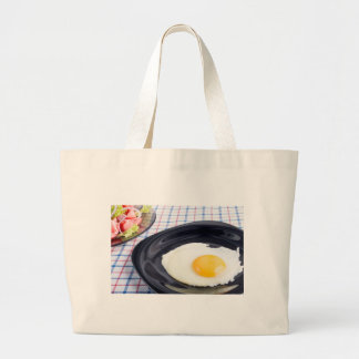 Fried egg with yolk on a black plate large tote bag