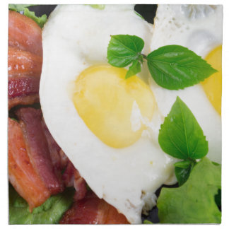 Fried eggs and bacon with herbs and lettuce napkin