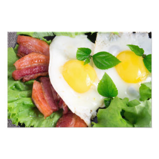 Fried eggs and bacon with herbs and lettuce photo print