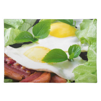 Fried eggs with herbs, lettuce and  bacon placemat