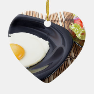 Fried eggs with yolk on a black plate and a salad ceramic heart ornament