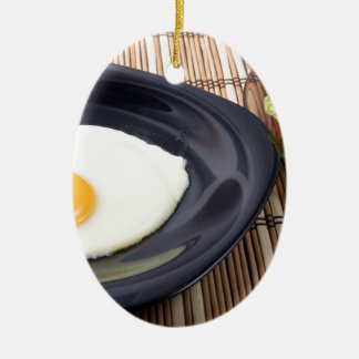 Fried eggs with yolk on a black plate and a salad ceramic oval ornament