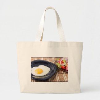 Fried eggs with yolk on a black plate and a salad large tote bag