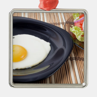 Fried eggs with yolk on a black plate and a salad Silver-Colored square ornament