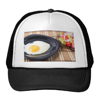 Fried eggs with yolk on a black plate and a salad trucker hat