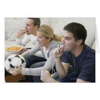 Friends watching TV with whistle, football and Card