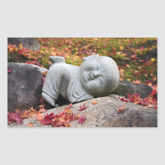 Funny Japanese monk statue with autumn leaves