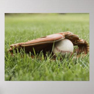Gant de base-ball avec la boule dans l'herbe poster