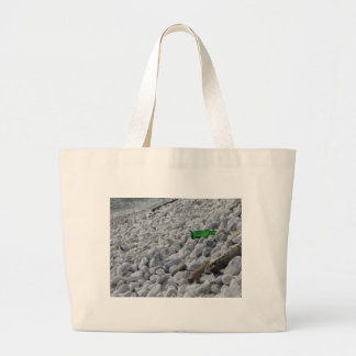 Garbage on the beach .Particular of a green bottle Large Tote Bag