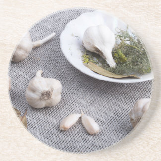 Garlic and spices on a gray fabric background coaster