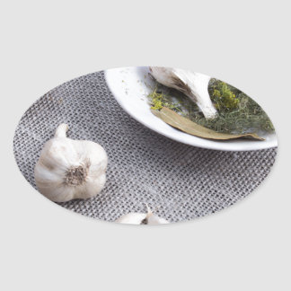 Garlic and spices on a gray fabric background oval sticker
