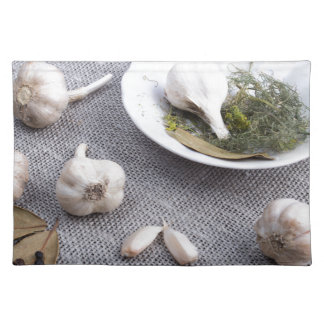 Garlic and spices on a gray fabric background placemat