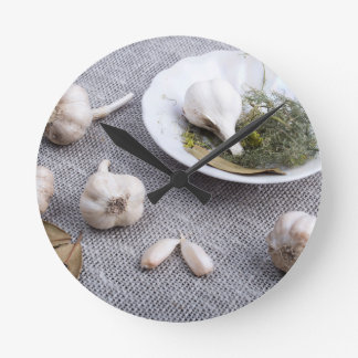 Garlic and spices on a gray fabric background round clock