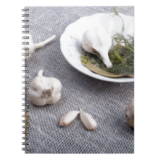 Garlic and spices on a gray fabric background spiral notebook