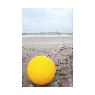 giant yellow buoy on beach canvas print