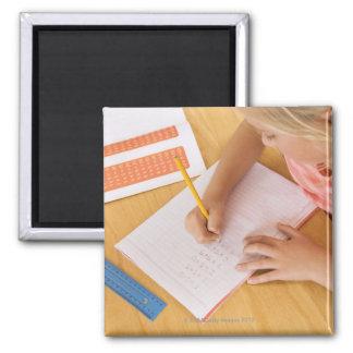 Girl doing homework magnet