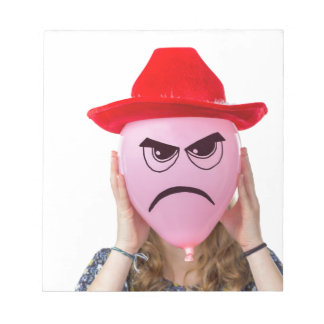 Girl holding pink balloon with angry face and hat notepads