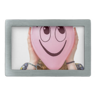 Girl holding pink balloon with smiling face belt buckle