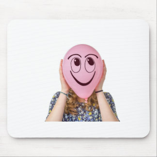 Girl holding pink balloon with smiling face mouse pad
