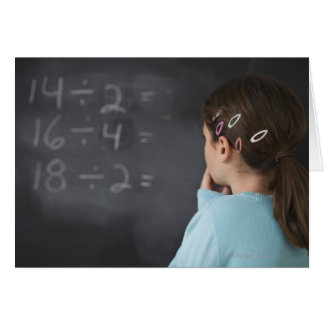 Girl looking at math equations on blackboard card