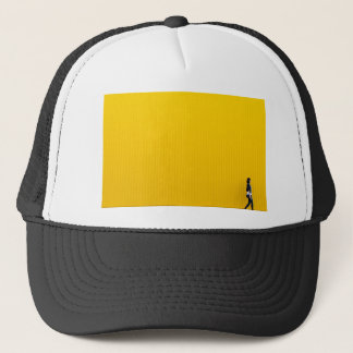 Girl Walking Against Enormous Yellow Wall Trucker Hat