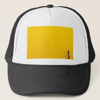 Girl Walking Against Enormous Yellow Wall Trucker Hat