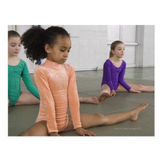 Girls stretching in gymnastics practice postcard