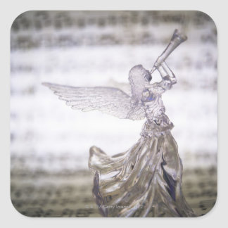 Glass angel playing trumpet and image of sheet square sticker