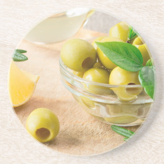 Glass cup with green pitted olives beverage coaster