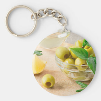 Glass cup with green pitted olives keychain