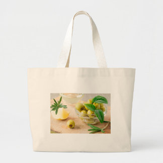 Glass cup with green pitted olives large tote bag
